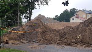 En bild från en byggarbetsplats, sandhögar och metallräcke syns.