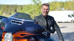 Anders Fagerholm sitter på sin motorcykel och tittar in i kameran.