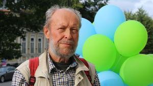 Eläkeikäinen mies Turun pääkirjaston edessä, kasvokuva.