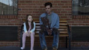 Nell (Violet Mcgraw) och Hugh Crain (Henry Thomas) sitter bredvid varandra på en bänk.