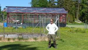 mats Nyman utanför ett växthus. Han har solglasögon på sig.
