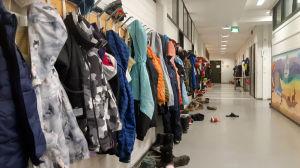 En korridor i en skola. På ena väggen hänger en lång rad med utekläder.