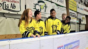 Några av spelarna i Kraft Hockey C-juniorer står utanför sargen i ishallen i Närpes
