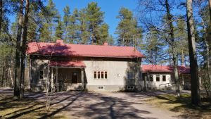 En stenbyggnad med rött tak omgiven av träd.