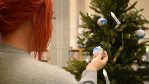 En kvinna med rött hår håller i en julgranskula som hänger i en julgran.