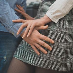 En man lägger händerna på en kvinnas höfter.