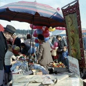 En man synar utbudet vid ett marknadsstånd. I bakgrunden syns ballonger.