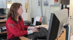 Kvinna i röd tröja sitter vid en dator.
