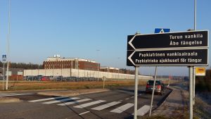 Skylt som visar att man ska svänga in till Åbo fängelse och Psykiatriska sjukhuset för fångar. Fängelset i Starrbacka är en byggnad i rödtegel, omgiven av en vit mur och taggtrådsstängsel.