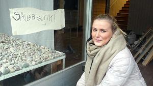 Emma Madsén på huk vid skyltfönstret till sin blivande salladsbar. Ett barn har skrivit en provisorisk affish på fönstret där det står salladsbutik.