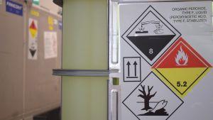 En stor tank med grönt innehåll, symboler för giftiga kemikalier på en lapp som sitter på tanken.