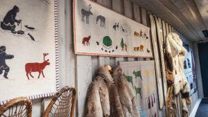 Kirjailuin koristeltuja seinävaatteita sekä turkisanorakkeja seinällä.