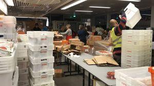 En man lyfter en låda, andra packar ur lådor.