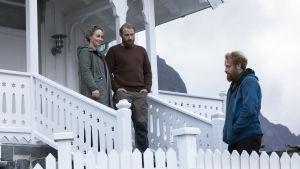 Karaktärerna Adam och Ingrid står på en fint målad trappa till sitt hus och tittar ner på Erik.