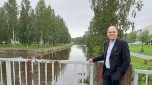 En man i kostym står på en bro.