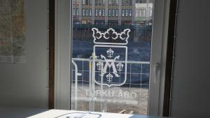 Åbo stads vapen klistrat på en glasdörr, i bakgrunden genom rutan skymtar torgparkeringsbygget.