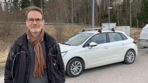 Dominicus Björkstam står på en bensinstation, ser in i kameran och ler. Bakom sig har han en vit bil med ett släp. Han har på sig en svart rock och en halsduk.