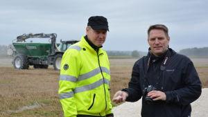 Juhs Ääri och Henri Vaarala står på en åker  - i bakgrunden en traktor.
