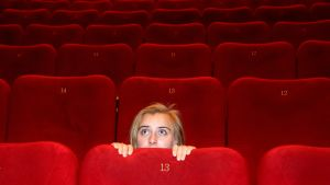 En kvinna i en tom biografsal kryper ihop bakom stolen och tittat försiktigt fram.