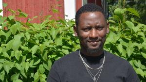 Hassan Barry i Vörå. Han står i svart tröja framför en grön häck. I bakgrunden syns ett rött hus med vita knutar.
