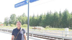Man framför tågspår vid Jakobstad-Pedersöre tågstation.