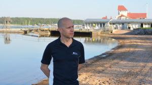 En man står vid en strand, i bakgrunden ett hopptorn och en träbyggnad.