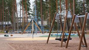 skolgård med gungor ock klätterställningar.