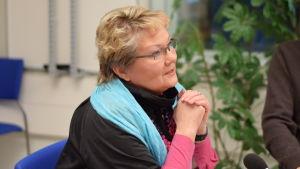 Merja Laaksonen pratar vid ett bord.
