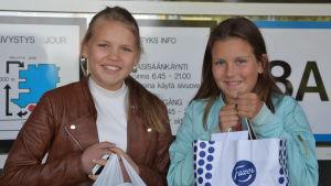 Två flickor med kassar i händerna utanför en sjukhusingång.