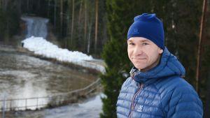 En man i blå mössa- och rock i förgrunden. I bakgrunden syns början till skidspår med snö.