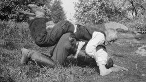 """Två män leker """"ryggbördan"""", där den ena ligger på den andras rygg, Den undre ska försöka stiga upp, den andra ska hindra honom att göra det. Bilden är tagen 1929 i Strömfors, Kungsböle."""