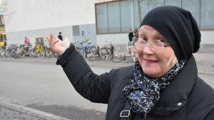 Virpi Tervonen, en dam med glasögon och svart mössa, pekar mot Åbo huvudbibliotek.