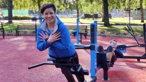 En kvinna och en man motionerar med redskap i en motionspark.