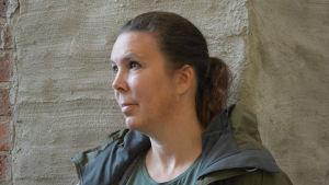 Kvinna vid stenvägg.