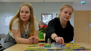 Lina pratar och ser glad ut, Matilda flyttar en blå knapp på Kimble spelet