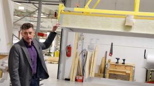Christian Juslin visar upp en säng som kan fällas in i taket.