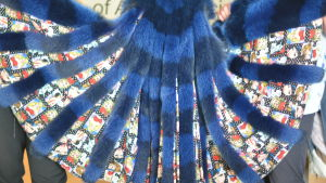 Svart- och blårandiga pälsdetaljer på en klänning med serietidningsmönster