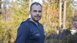 Martin Norrgård tittar in i kameran iklädd mörkblå sportjacka där det står SWE.