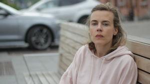 Vit kvinna med ljust hår sitter på en bänk framför två silverfärgade bilar.