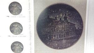 Frimärke och postkort av Finlands första fotografi, vilket Henrik Cajander 1842 tog av det Nobelska huset i Åbo.