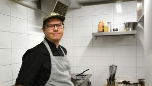 Joakim Strand står i ett restaurangkök bredvid spisar.