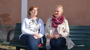 Eija och Pilvi på en bänk i solskenet.