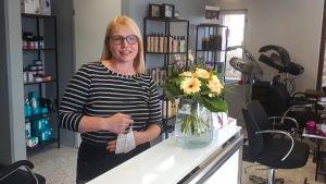 En kvinna står bakom en betjäningsdisk inne i en frisörsalong.