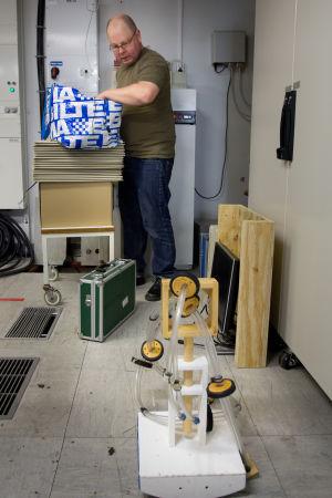 Dosentti Jarmo Malinen katsoo lattialla seisovaa äänenkeräimen osaa.