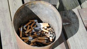 Rostig plåthink med cigarettfimpar utomhus.