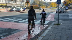 Två cyklister vid en röd cykelled.