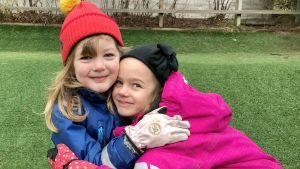 Två flickor i varma ytterkläder kramas och ser glada ut.
