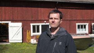Martin Snickars står framför en röd gammal ladeugårdf på Husö