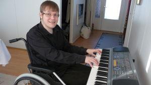 Tommy Lundström sitter i rullstol, spelar piano och tittar mot kameran
