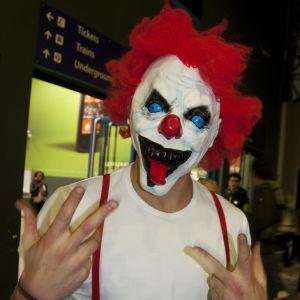 Person utklädd till clown, med en clownmask med rött hår och stora utstående blåa ögon.